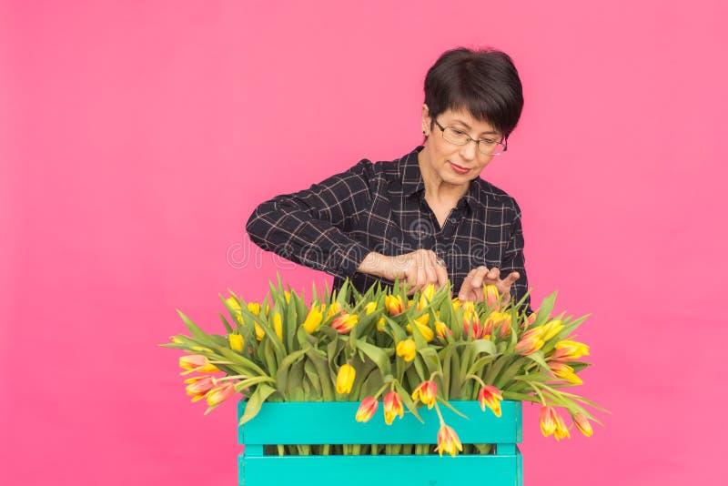 Mujer de mediana edad hermosa con los tulipanes amarillos en fondo rosado Floristics, días de fiesta y concepto de los regalos fotografía de archivo