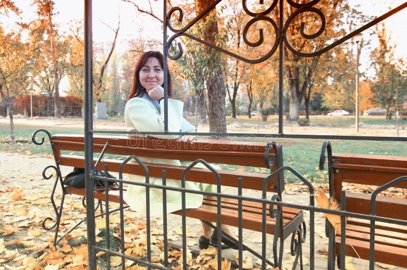 Mujer de mediana edad hermosa que se sienta en el banco en parque Humor del otoño Una mujer se está sentando en un banco en el me imagenes de archivo