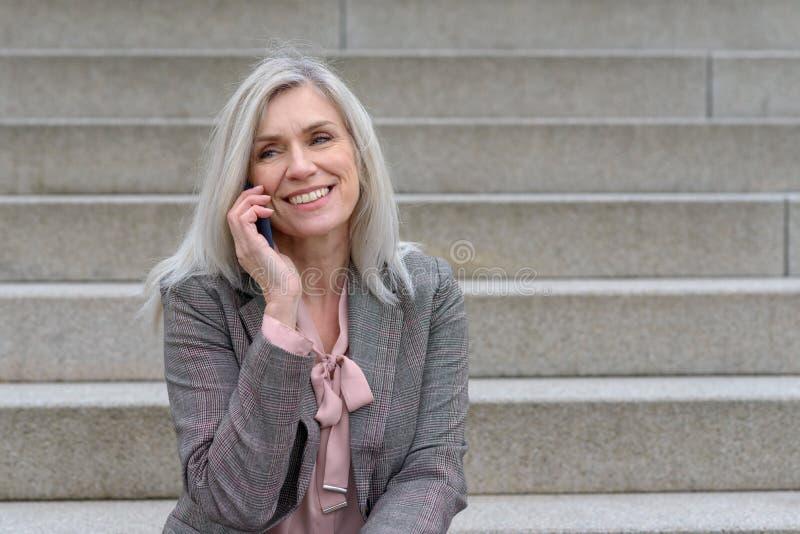 Mujer de mediana edad que escucha una llamada de teléfono fotos de archivo