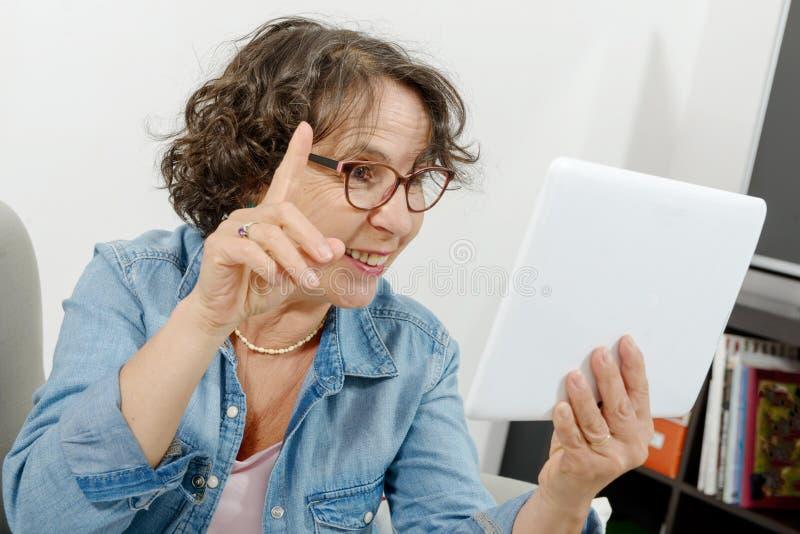 Mujer de mediana edad que hace una llamada distante en Internet fotos de archivo libres de regalías