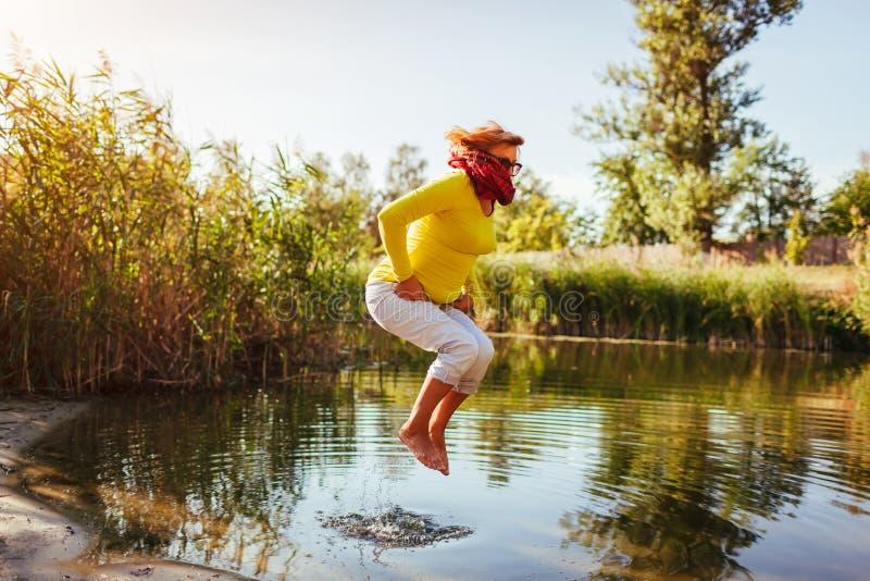 Mujer de mediana edad que salta en la orilla del río el día del otoño Señora mayor feliz que se divierte que camina en el bosque imagen de archivo