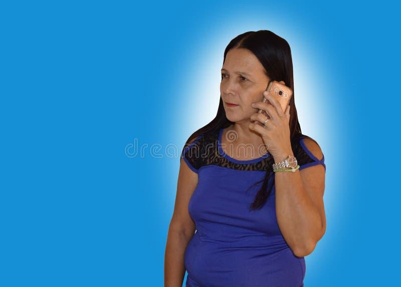 Mujer de mediana edad que tiene una llamada de teléfono fotografía de archivo