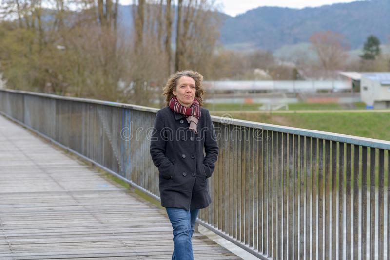 Mujer de mediana edad sana de moda que camina al aire libre fotografía de archivo