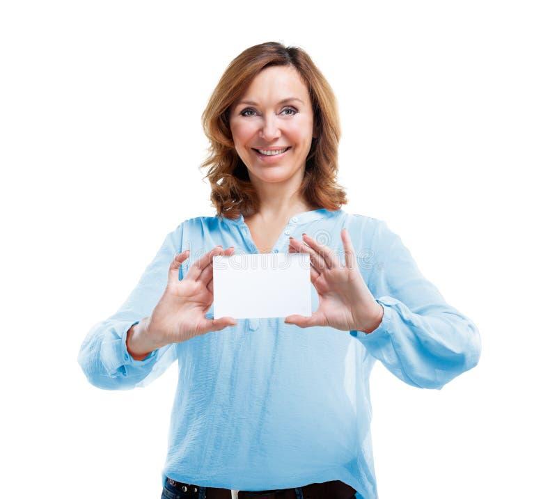 Mujer de mediana edad sonriente amistosa aislada en el fondo blanco foto de archivo