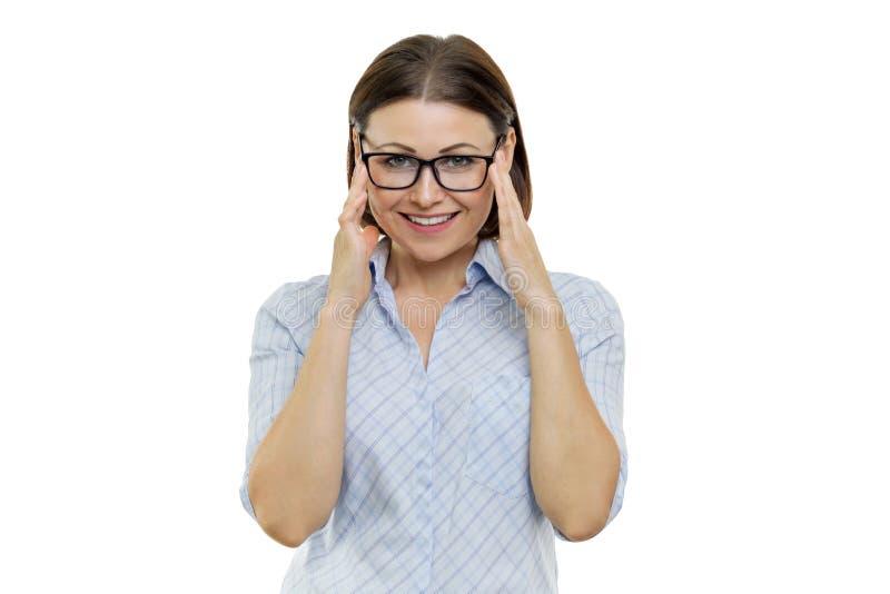 Mujer de mediana edad sonriente con los vidrios que miran la cámara, manos cerca de los vidrios, fondo aislado, blanco imagenes de archivo