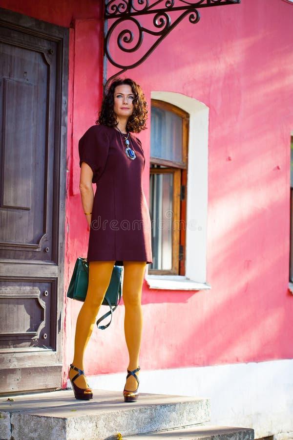 Mujer de mediana edad sonriente hermosa en un vestido de Borgoña y un bolso verde en el pórtico de una casa vieja imágenes de archivo libres de regalías