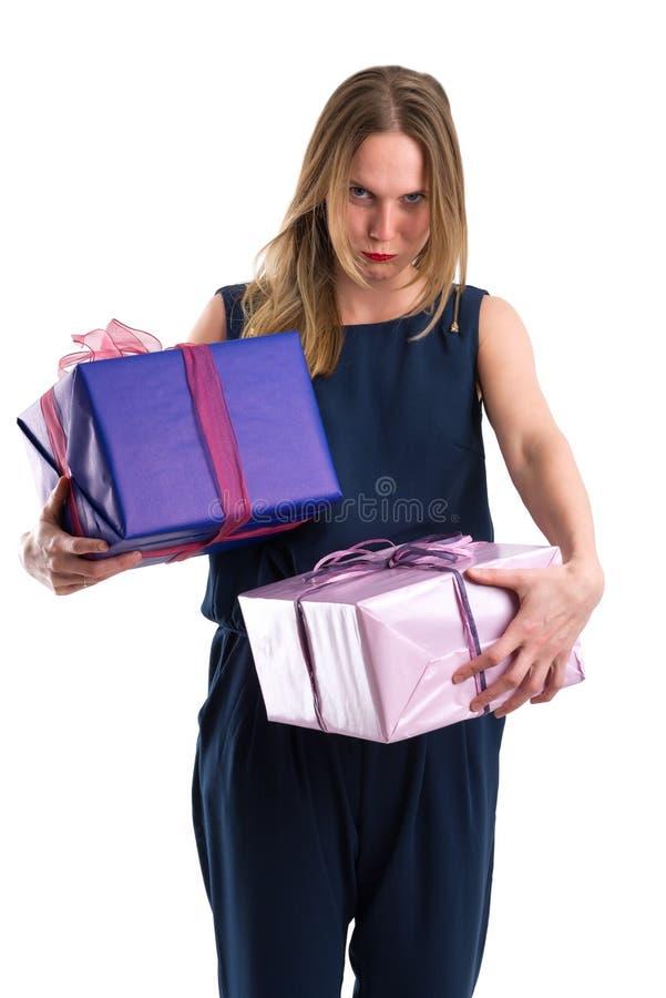 Mujer de mirada contrariedad que lleva los paquetes pesados del regalo imágenes de archivo libres de regalías