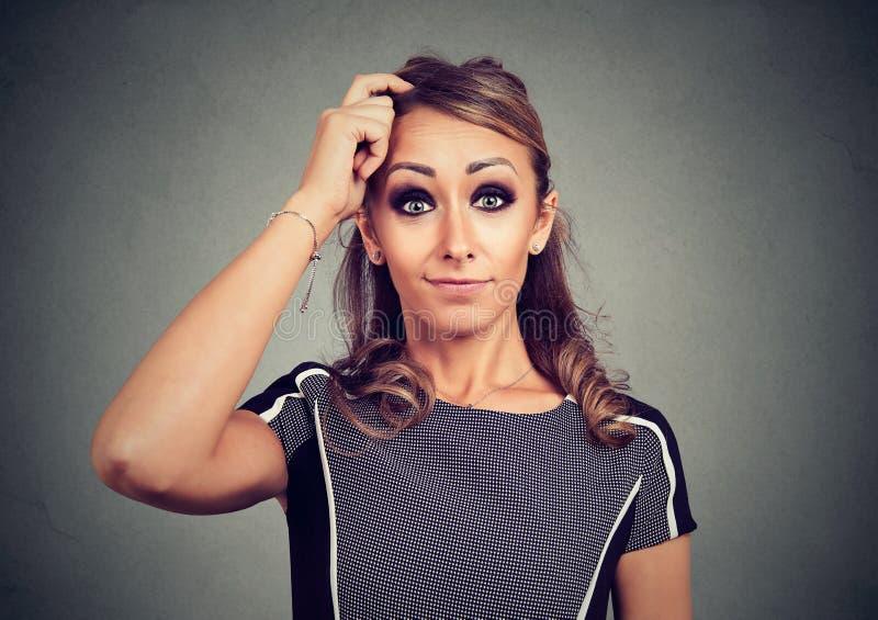 Mujer de mirada divertida confusa que rasguña la cabeza fotos de archivo