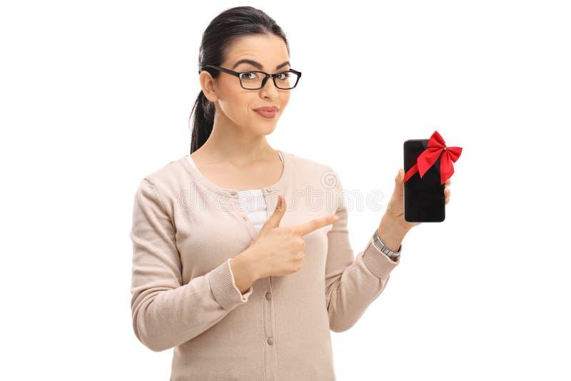 Mujer de mirada elegante que muestra un teléfono envuelto con la cinta roja fotografía de archivo
