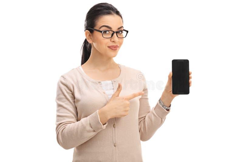 Mujer de mirada elegante que muestra un teléfono y señalar imagen de archivo