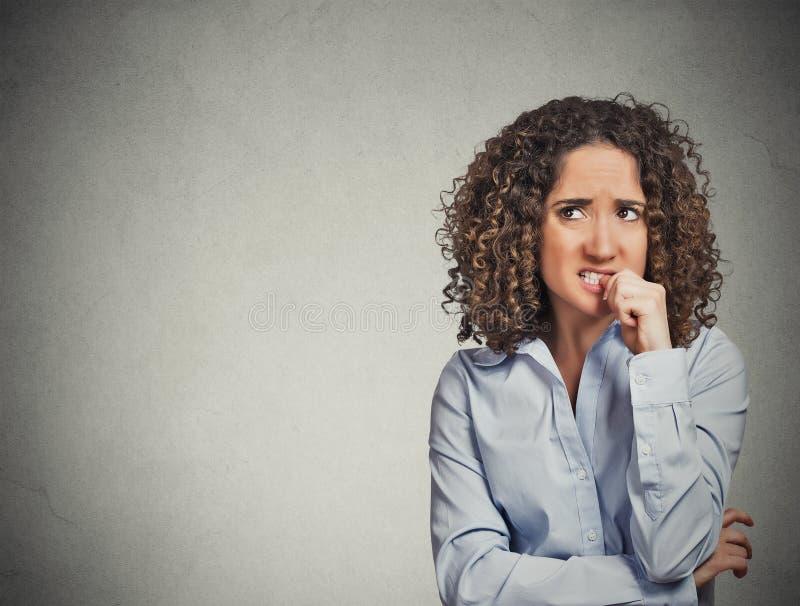 Mujer de mirada nerviosa que muerde sus uñas que anhelan algo foto de archivo libre de regalías