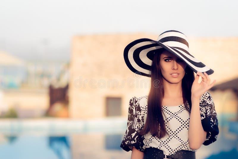 Mujer de moda con el sombrero grande del verano por la piscina imagen de archivo libre de regalías