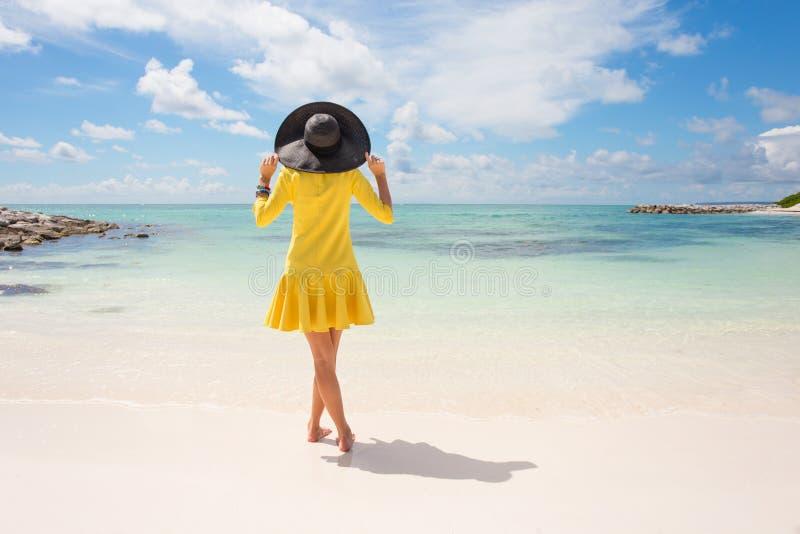 Mujer de moda con el sombrero negro del verano y el vestido amarillo en la playa imágenes de archivo libres de regalías