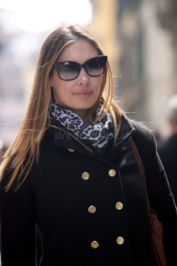Mujer de moda con la capa, el bolso, la bufanda y las gafas de sol imagen de archivo libre de regalías