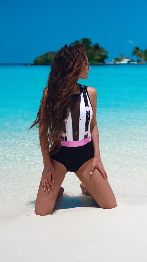 Mujer de moda en bikini que broncea en la playa tropical Muchacha delgada bonita que presenta en la isla exótica por el océano  imagen de archivo