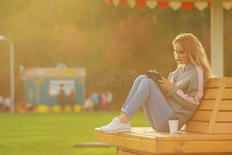 Mujer de moda en sentarse en el banco en parque de la ciudad caf para llevar de consumici n y - Banco para sentarse ...