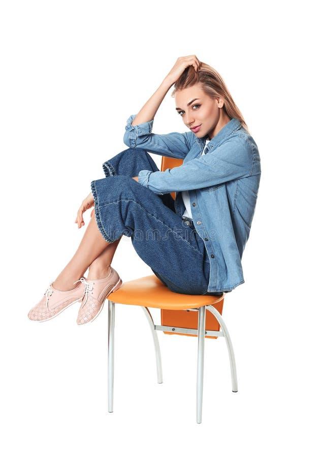 Mujer de moda en zapatos elegantes en silla contra blanco fotos de archivo libres de regalías