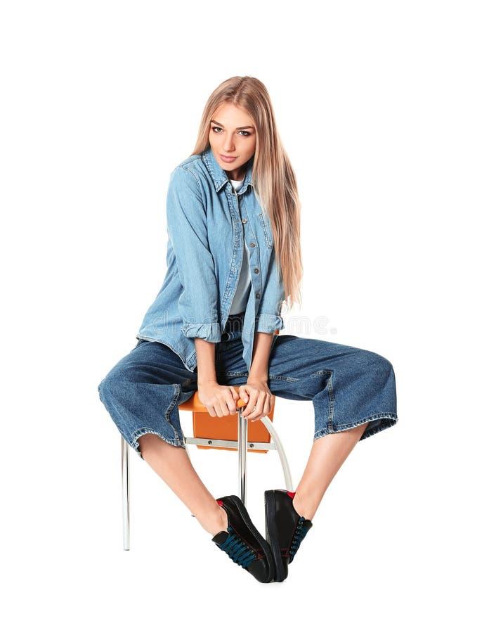 Mujer de moda en zapatos elegantes en silla contra blanco imagen de archivo libre de regalías