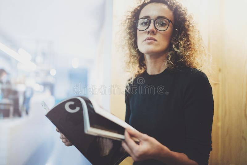 Mujer de moda encantadora con los vidrios de los ojos que lee sentarse de la revista interior en café urbano Retrato casual de ba fotos de archivo