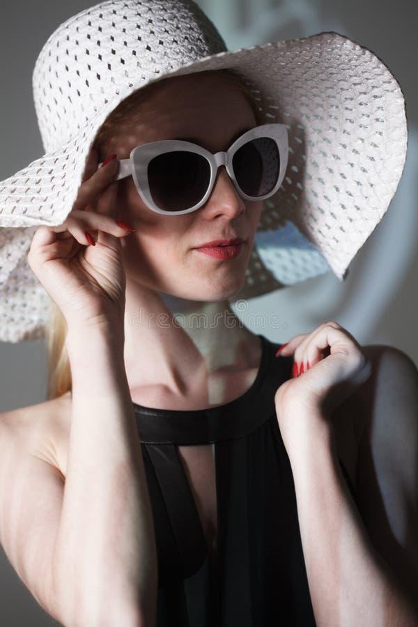 Mujer de moda hermosa joven con maquillaje de moda En cámara de mirada modelo, lentes elegantes que llevan, sombrero La moda feme fotos de archivo