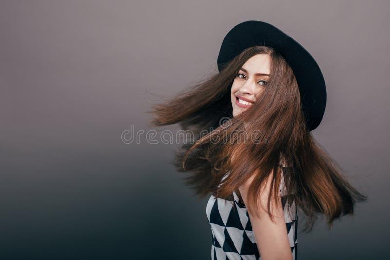 Mujer de moda hermosa joven con maquillaje de moda en sombrero negro y vidrios en el fondo gris En cámara de mirada modelo, w imágenes de archivo libres de regalías