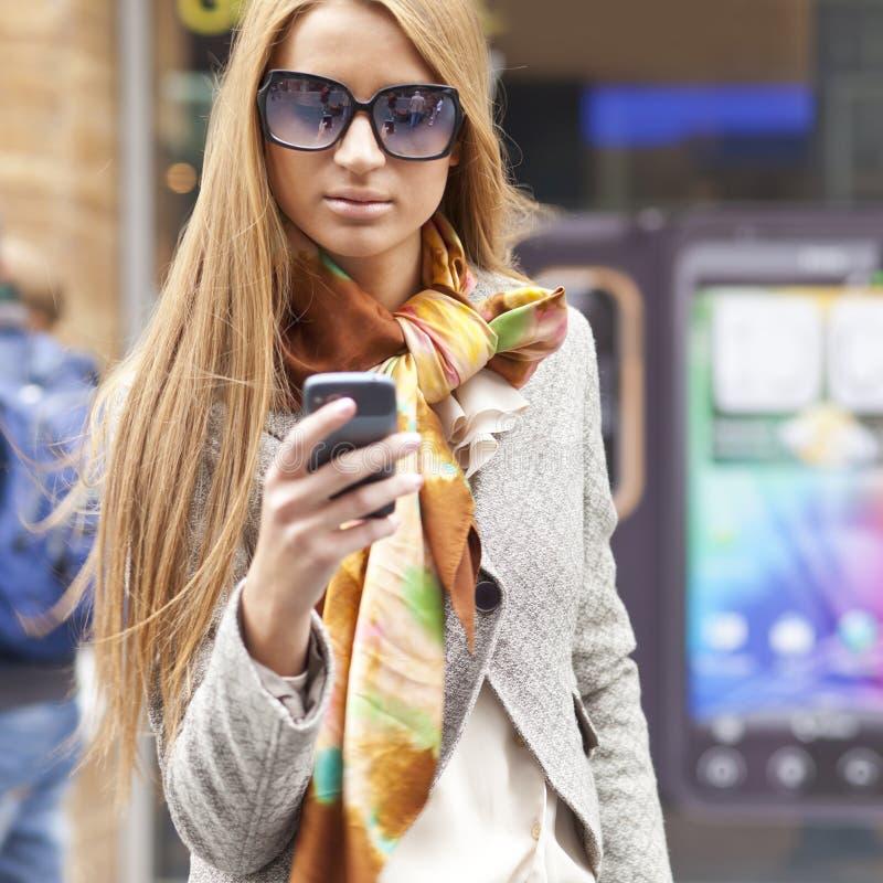 Mujer de moda joven con smartphone en la calle imagen de archivo