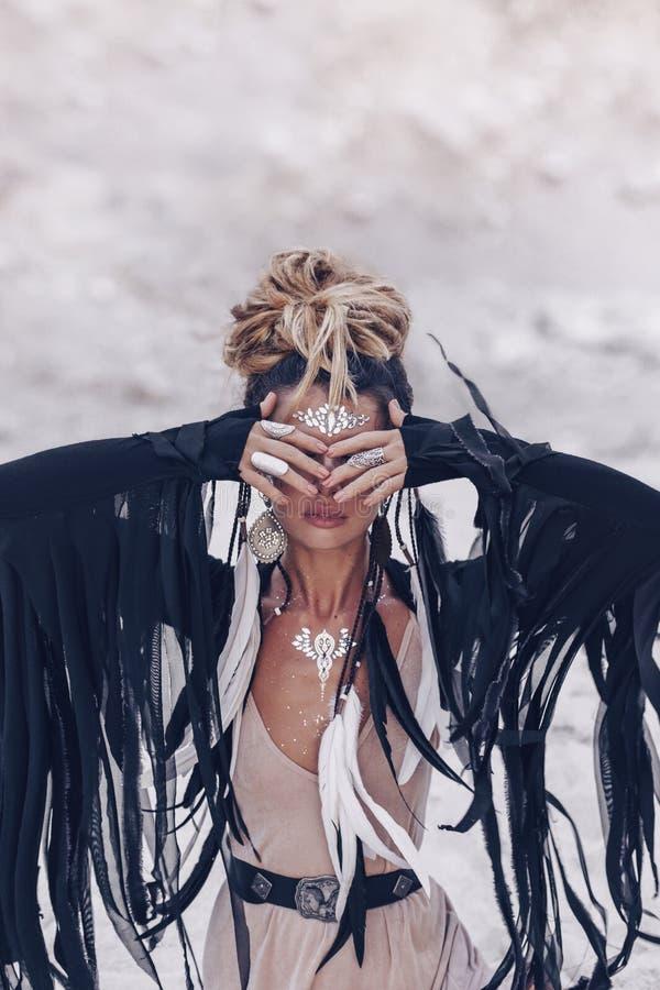 Mujer de moda joven hermosa del estilo del boho que se sienta en el beac imágenes de archivo libres de regalías