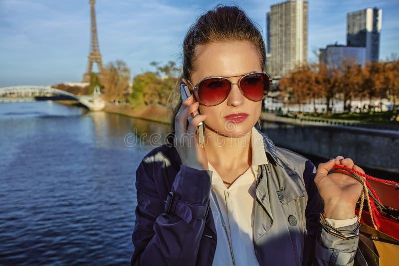 Mujer de moda joven que habla en el teléfono celular cerca de torre Eiffel imagen de archivo libre de regalías
