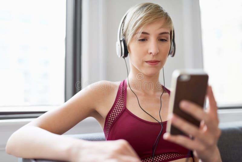 Mujer de moda que escucha un meditaion app como parte de su rutina de la ma?ana del mindfulness imagen de archivo libre de regalías