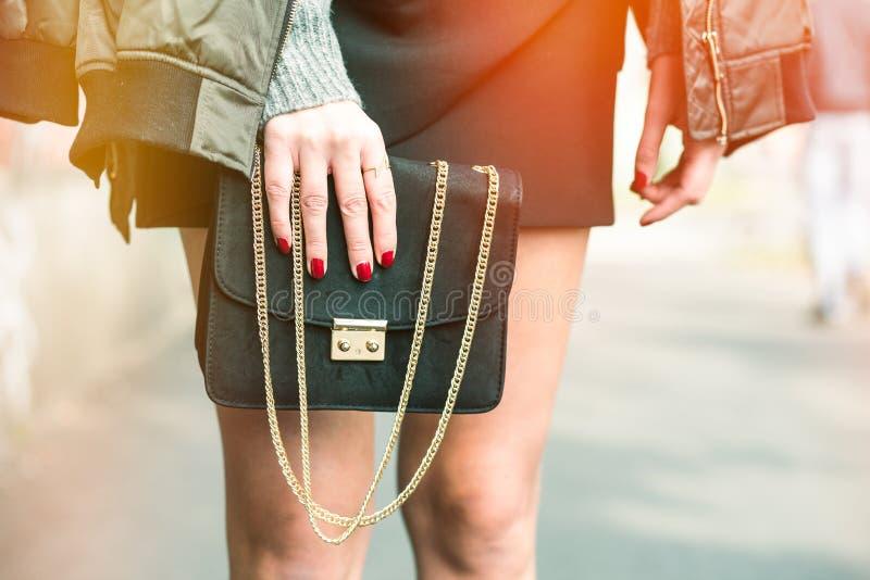 Mujer de moda que lleva una chaqueta de bombardero verde oliva, un reloj de oro y un bolso de moda negro foto de archivo libre de regalías