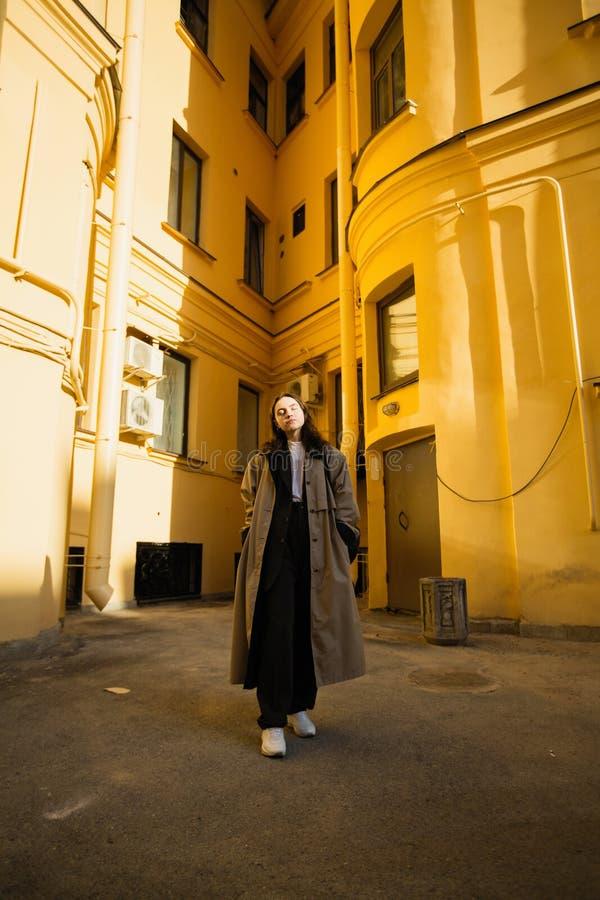 Mujer de moda que presenta en la yarda de casas de la ciudad fotos de archivo libres de regalías