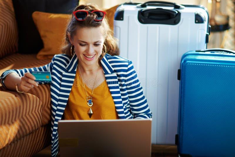 Mujer de moda sonriente con los boletos de reservación de la tarjeta de crédito en el ordenador portátil imágenes de archivo libres de regalías