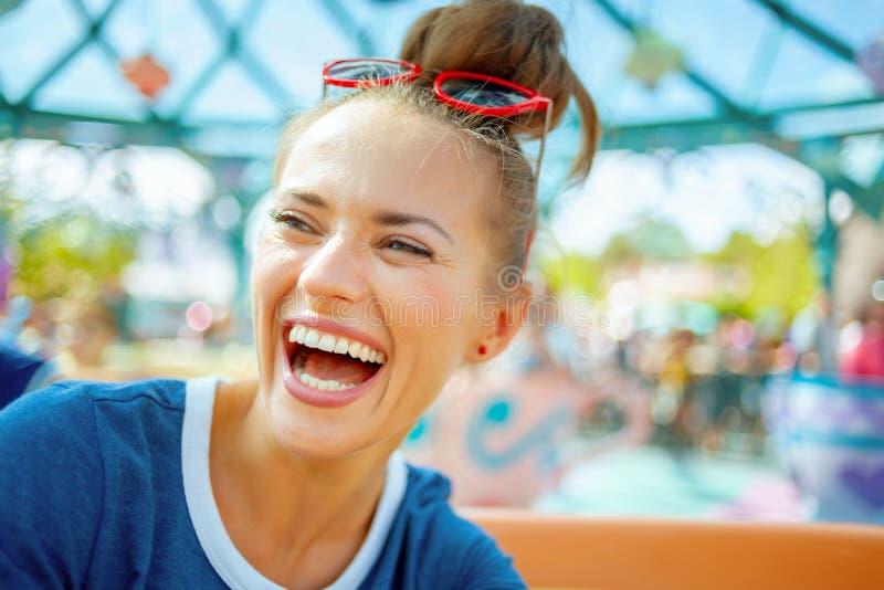 Mujer de moda sonriente en parque de atracciones que disfruta de paseo foto de archivo