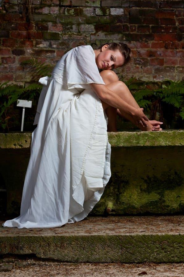 Mujer de Mournfull en el vestido blanco que se sienta en un banco de piedra fotos de archivo libres de regalías