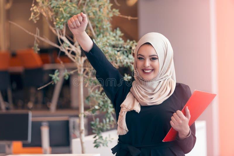 Mujer de negocios árabe que sostiene una carpeta en oficina de lanzamiento moderna fotos de archivo