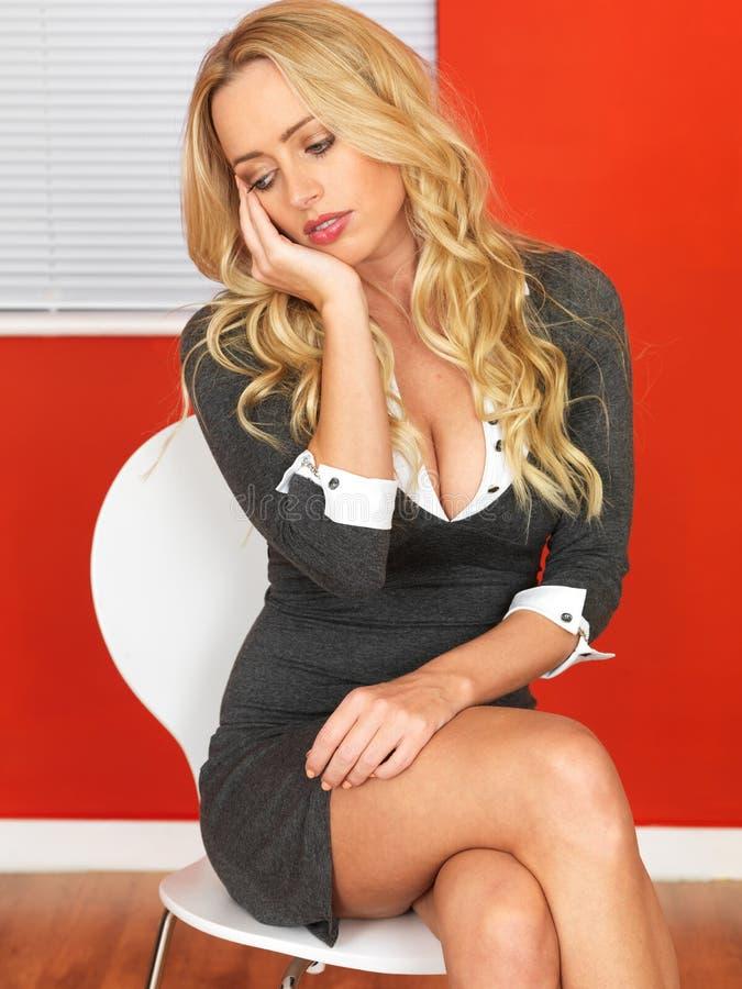 Mujer de negocios aburrida atractiva que se sienta en una silla fotos de archivo libres de regalías
