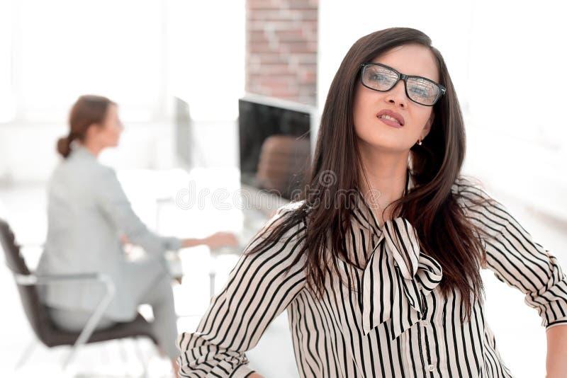 Mujer de negocios acertada en fondo borroso de la oficina imagen de archivo