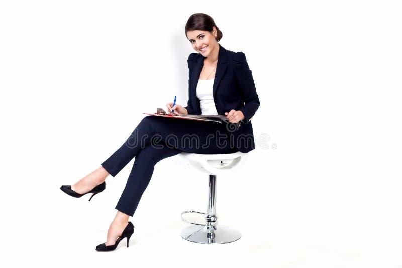 Mujer de negocios acertada feliz en silla de la oficina en el fondo blanco fotos de archivo