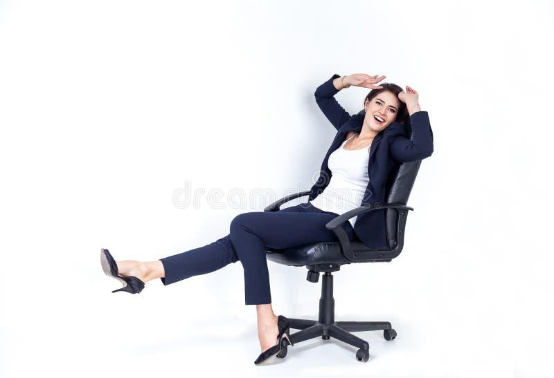 Mujer de negocios acertada feliz en silla de la oficina en el fondo blanco imagenes de archivo