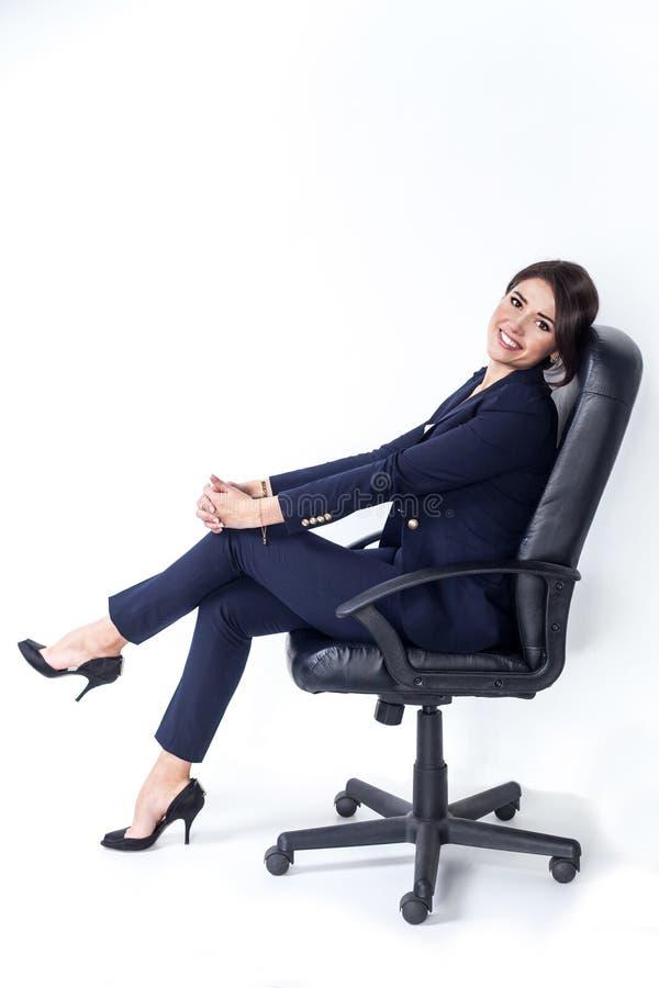 Mujer de negocios acertada feliz en silla de la oficina en el fondo blanco imagen de archivo libre de regalías