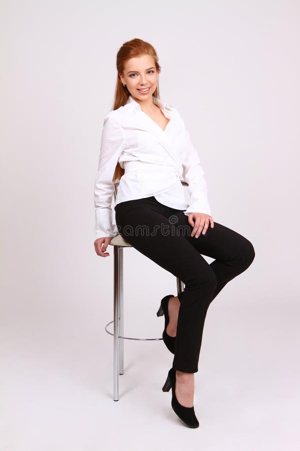 Mujer de negocios acertada feliz en silla en el fondo blanco imágenes de archivo libres de regalías