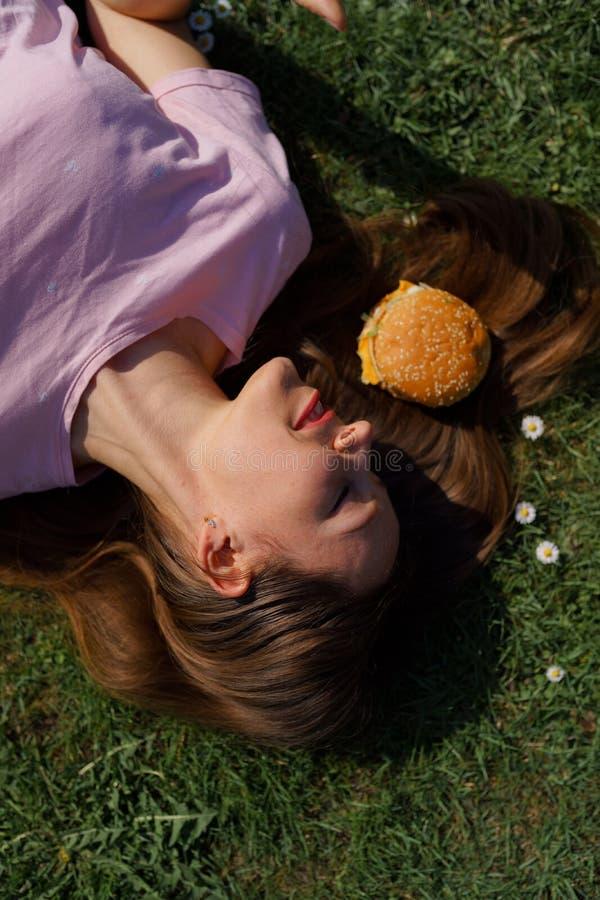 Mujer de negocios acertada que miente en la hierba con el cheesburger de la hamburguesa de los alimentos de preparación rápida en imagenes de archivo