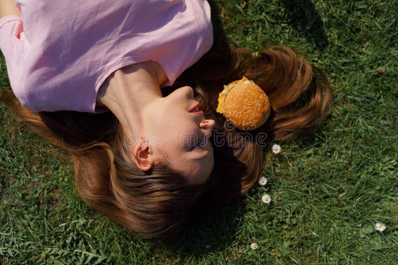 Mujer de negocios acertada que miente en la hierba con el cheesburger de la hamburguesa de los alimentos de preparaci?n r?pida en imagenes de archivo