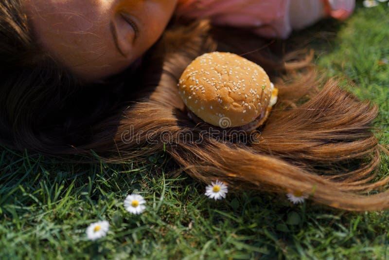 Mujer de negocios acertada que miente en la hierba con el cheesburger de la hamburguesa de los alimentos de preparaci?n r?pida en fotografía de archivo libre de regalías