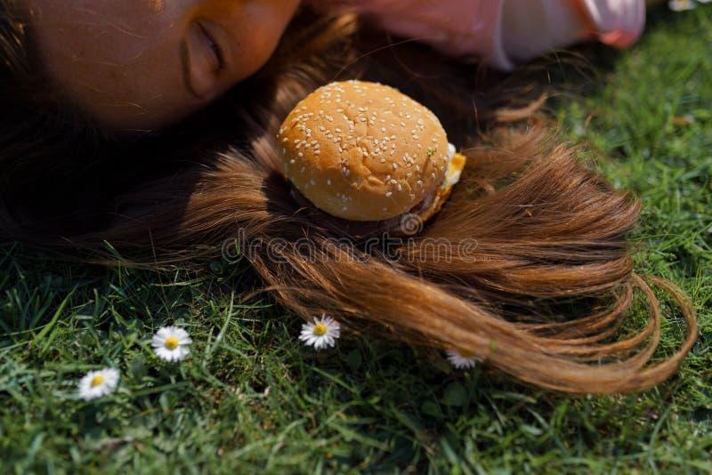 Mujer de negocios acertada que miente en la hierba con el cheesburger de la hamburguesa de los alimentos de preparaci?n r?pida en imagen de archivo