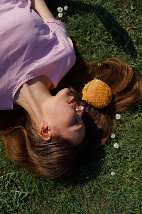 Mujer de negocios acertada que miente en la hierba con el cheesburger de la hamburguesa de los alimentos de preparaci?n r?pida en fotos de archivo libres de regalías