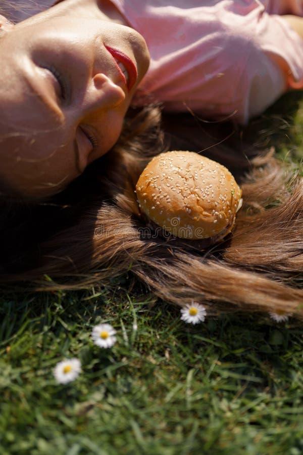 Mujer de negocios acertada que miente en la hierba con el cheesburger de la hamburguesa de los alimentos de preparaci?n r?pida en imagen de archivo libre de regalías