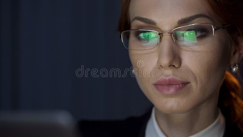 Mujer de negocios acertada que mira el ordenador portátil, reflexión de la pantalla en lentes fotos de archivo