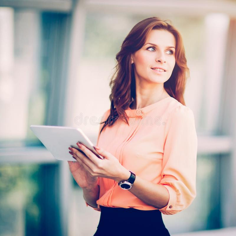 Mujer de negocios acertada que sostiene una tableta digital en la oficina imágenes de archivo libres de regalías