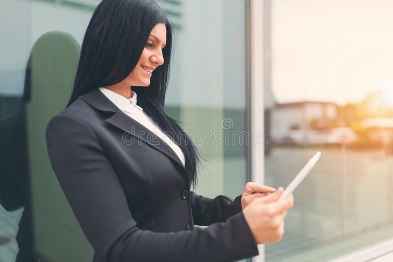 Mujer de negocios acertada que trabaja con la tableta en un ambiente urbano foto de archivo libre de regalías